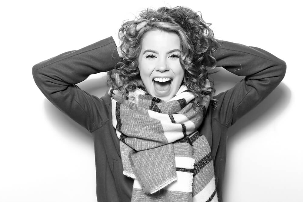 A black and white photo of a woman with curly hair and a skin softening glam filter is applied to the image