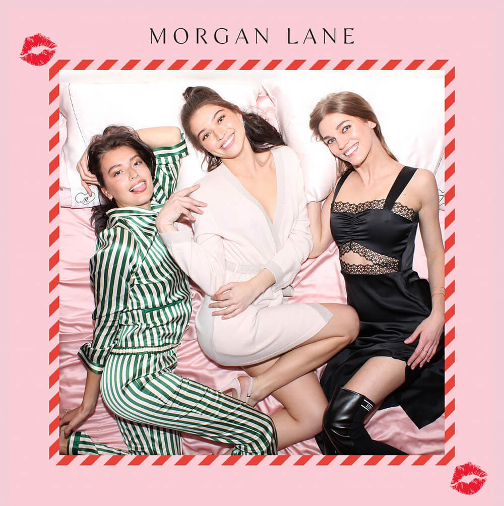 three woman pose in pajamas in the Morgan Lane Overhead photo booth photo activation