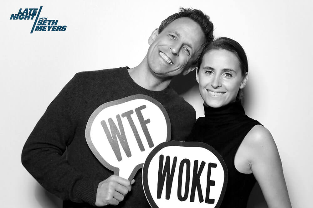 "Seth Meyers and wife Alexa Ashe pose in a black and white image with a photo booths sign prop that reads ""WTF"" and ""Woke"""