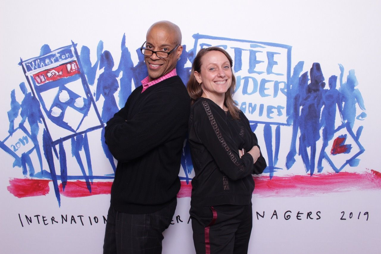 two employees pose in estee lauder photo booth in san francisco
